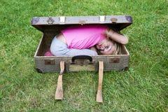 Fille blonde d'enfant à l'intérieur d'une valise sur la pelouse d'herbe verte Photographie stock libre de droits