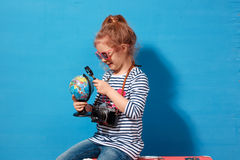 Fille blonde d'enfant avec l'étude rose de valise de vintage le globe Concept de voyage et d'aventure Images stock