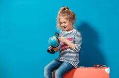 Fille blonde d'enfant avec l'étude rose de valise de vintage le globe Concept de voyage et d'aventure Photographie stock