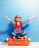Fille blonde d'enfant avec la valise rose de vintage prête pour l'été va Photos stock