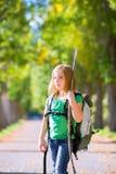 Fille blonde d'enfant d'explorateur marchant avec le sac à dos dans des arbres d'automne Images libres de droits