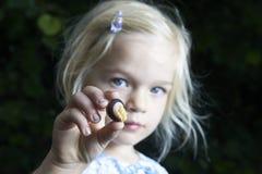 Fille blonde d'enfant montrant et étudiant le petit jeune escargot Images stock