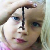 Fille blonde d'enfant tenant le ver de terre Image libre de droits