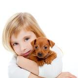 Fille blonde d'enfants avec pinscher de chiot de crabot le mini Photographie stock libre de droits