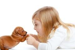 Fille blonde d'enfants avec pinscher de chiot de crabot le mini Image libre de droits