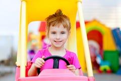 Fille blonde d'enfants conduisant le véhicule de jouet Image libre de droits