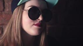 Fille blonde dans de grandes lunettes de soleil posant devant le mur de briques dans la chambre noire banque de vidéos
