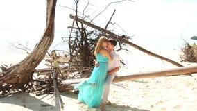 Fille blonde dans des baisers bleus de robe avec passion Guy Sitting sur le rondin parmi les arbres secs banque de vidéos