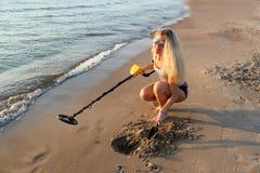 Fille blonde dans des lunettes de soleil avec le détecteur de métaux  Photographie stock