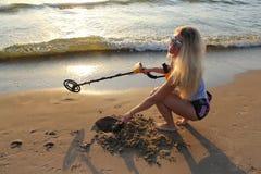 Fille blonde dans des lunettes de soleil avec le détecteur de métaux  Photographie stock libre de droits