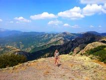 Fille blonde dans des lunettes de soleil avec le photocamera marchant dans les montagnes dans Bulgary, Images stock