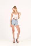 Fille blonde dans des shorts de jeans Photo stock