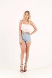 Fille blonde dans des shorts de jeans Photo libre de droits