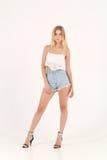 Fille blonde dans des shorts de jeans Images libres de droits