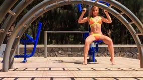 fille blonde dans des trains de bikini sur le simulateur de pile de poids en parc clips vidéos