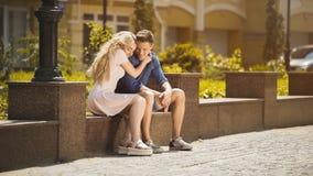 Fille blonde dans l'amour étreignant l'ami, appréciant la date en parc le jour ensoleillé d'été Photos stock