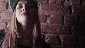 Fille blonde dans la relance d'houblon de hanche posant devant le mur de briques dans la chambre noire banque de vidéos