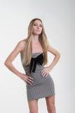 Fille blonde dans la robe rayée avec la proue noire Photographie stock libre de droits