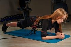 Fille blonde dans le costume de SME faisant l'exercice de planche sur le tapis de sports lueur Images stock