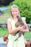 Fille blonde dans le jardin avec des poulets photo libre de droits