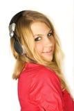 Fille blonde dans le sourire d'écouteurs d'isolement Images libres de droits