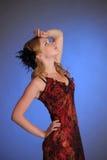 Fille blonde dans une longue robe rouge avec des vues langoureuses Photographie stock libre de droits