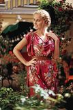 Fille blonde dans une robe rose avec des fleurs Photos libres de droits