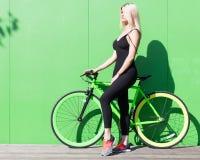 Fille blonde de beauté avec de longs cheveux dans un équipement sexy bien ajusté noir et des espadrilles posant avec une difficul Photo libre de droits