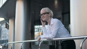 Fille blonde de belle jeune femme d'affaires en verres appelant par le téléphone au centre d'affaires de fond Image libre de droits