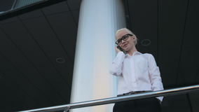 Fille blonde de belle jeune femme d'affaires en verres appelant par le téléphone au centre d'affaires de fond Photo libre de droits