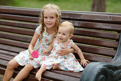 Fille blonde de deux soeurs avec du charme s'asseyant sur un banc dans le summe Photos stock