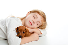 Fille blonde de gosse dormant avec le mini animal familier de pinscher Photographie stock