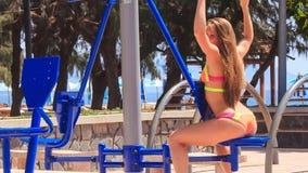 fille blonde de postérieur dans des trains de bikini sur le simulateur de pile de poids clips vidéos