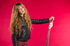Fille blonde de rock avec la guitare basse sur le rouge Images stock