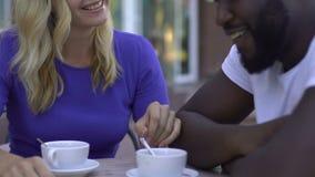 Fille blonde de sourire flirtant avec son ami afro-américain pendant la date en café clips vidéos