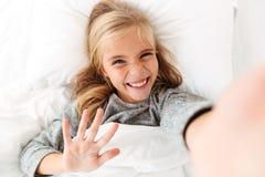 Fille blonde de sourire heureuse prenant le selfie tout en se situant dans le lit Photos stock