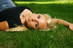 Fille blonde - dents blanches dans l'herbe Photographie stock
