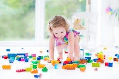 Fille blonde drôle d'enfant en bas âge s'asseyant sur le plancher dans le désordre photographie stock