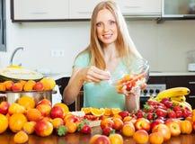 Fille blonde faisant cuire la salade de fruits avec des fruits images libres de droits