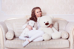 Fille blonde foncée sexy étreignant l'ours de nounours Photographie stock libre de droits