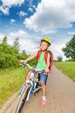 Fille blonde heureuse avec des tresses dans le casque de bicyclette Images stock