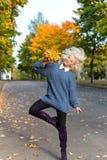 Fille blonde heureuse de bel amusement sautant et ayant l'amusement en parc d'automne avec un bouquet des feuilles colorées lumin images libres de droits