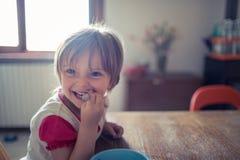 Fille blonde heureuse de fille avec des yeux bleus souriant tout en jouant sur le plancher en bois de salon Famille décontractée  Images stock