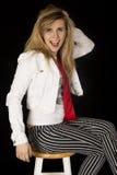 Fille blonde heureuse s'asseyant sur une bouche de selles ouverte Photographie stock libre de droits