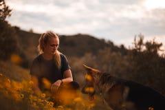 Fille blonde jouant avec le chien de berger allemand dans un domaine des fleurs jaunes images stock