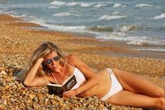 Fille blonde lisant un livre Photographie stock