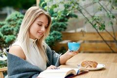 Fille blonde lisant un livre tout en buvant du café sur le salon du ` s de café d'extérieur images stock