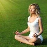 Fille blonde méditant sur l'herbe verte. Belle allocation des places de jeune femme dans la pose de yoga du lotus en parc. Photographie stock libre de droits