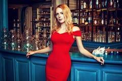 Fille blonde magnifique dans la robe rouge de mode restant au narguilé b photo libre de droits