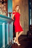 Fille blonde magnifique - modèle - dans des talons hauts rouges de robe et longtemps photos stock